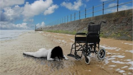Disabled woman poses naked on beach
